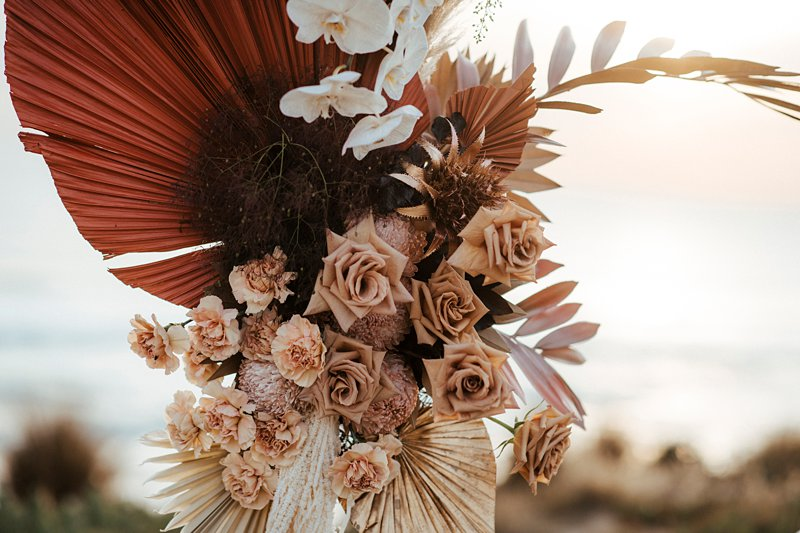 Rust and peach dried wedding flowers, Beachside styled wedding set up, sunpalms,