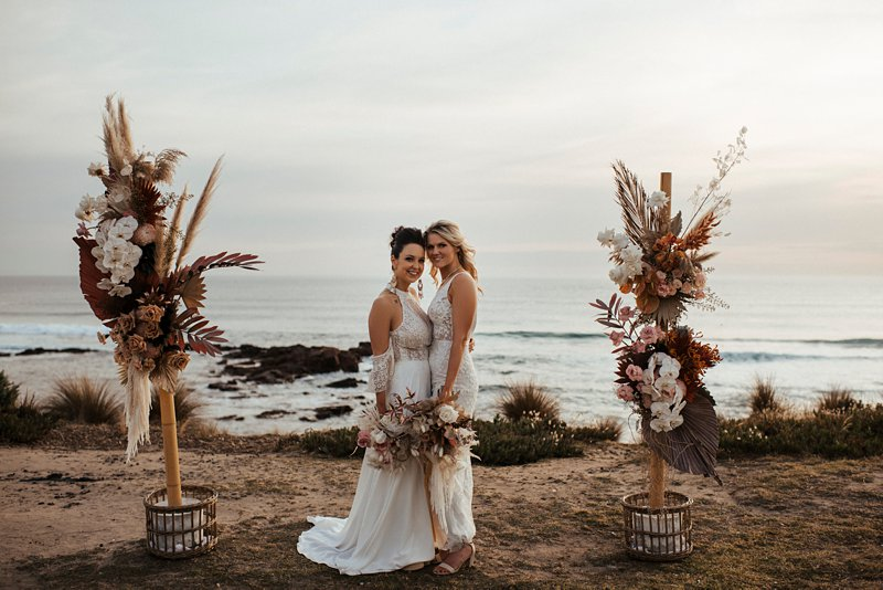 beachside wedding ceremony set up, same sex beach wedding, clifftop rust and peach flower ceremony setup