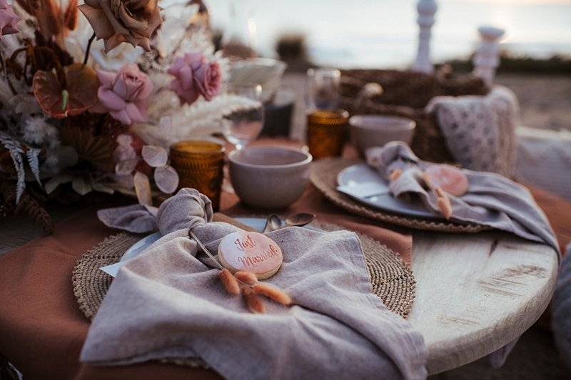 beachside clifftop wedding feast, wedding sunset picnic, sunset wedding, boho styled wedding feast, rust tones wedding